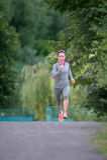 Biegacz żeńskiej atlety bieg na parkowym śladzie Kobiety sprawności fizycznej joggi zdjęcia royalty free