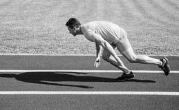 Biegacz chwytający w ruchu zaraz po początkiem rasa Biegacza sprintu rasa przy stadium Dlaczego zaczynać biegać Zwiększenie prędk zdjęcia stock