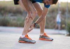 Biegacz dotyka bolesną kręconą lub łamaną kostkę obraz royalty free
