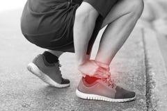 Biegacz dotyka bolesną kręconą lub łamaną kostkę fotografia royalty free