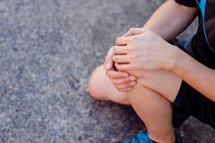 Biegacz dotyka bolesnego kolano Atleta biegacza stażowy wypadek Sporta działający kolanowy zwichnięcie obraz stock