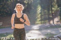 Biegacz kobieta słucha muzyka zaczyna biegać w być ubranym słuchawki zdjęcie stock