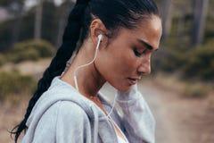 Biegacz słuchająca muzyka podczas outdoors treningu zdjęcia royalty free