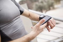 Biegacz synchronizuje jego mądrze telefon i zegarek fotografia royalty free