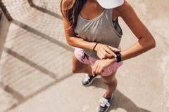 Biegacz używa mądrze zegarek monitorować jej postęp obraz stock