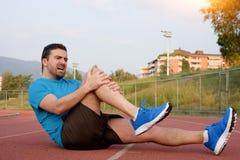 Biegacz z zdradzonym kolanem na śladzie obrazy stock