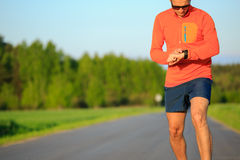 Biegacza szkolenie i sprawdzać stopwatch mądrze zegarek, przecinający countr Obrazy Royalty Free