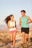 Biegacze - Aktywna sprawności fizycznej para biega śmiać się Obrazy Stock