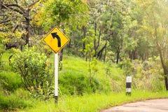 Biegen Zeichen auf dem Weg zwischen Hügel in Thailand nach links ab Stockbild