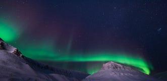 Biegunowa arktyczna Północnych świateł zorzy borealis nieba gwiazda w Norwegia Svalbard Longyearbyen miasta snowscooter górach obraz royalty free