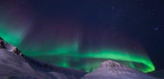 Biegunowa arktyczna Północnych świateł zorzy borealis nieba gwiazda w Norwegia Svalbard Longyearbyen miasta snowscooter górach zdjęcie royalty free