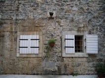 Biel żaluzje i średniowieczna kamienna ściana na starym grodzkim Budva Obrazy Stock