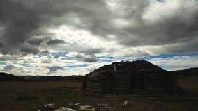 Biel chmurnieje na niebieskim niebie nad małym drewnianym domem zbiory
