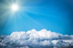 Biel chmury i jaskrawy słońce na niebieskim niebie Zdjęcie Stock