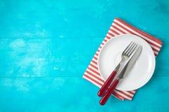 Biel czerwień i paskowaliśmy tablecloth na błękitnym drewnianym tle Odg?rny widok od above obrazy stock