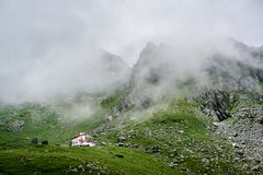 Biel domowa pozycja odizolowywająca w depresji zieleni trawiastych łąkowych pobliskich wspaniałych skalistych górach zakrywać w m Zdjęcia Stock