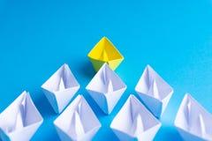 Biel i papierowa łódź statek w jeden kierunku na błękitnym tle lub obrazy stock