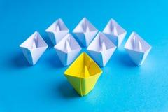 Biel i papierowa łódź statek w jeden kierunku na błękitnym tle lub obraz royalty free