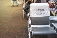 Biel i popielaty piority sadzamy blisko bramy w lotnisku z plama pasażerami za, Tajlandzki i Chiński język znaczy obrazy royalty free