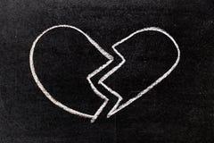 Biel kredy ręki rysunek w złamane serce kształcie na blackboard fotografia royalty free