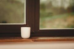 Biel pojedyncza herbata lub kawowy kubek na okno Fotografia Royalty Free