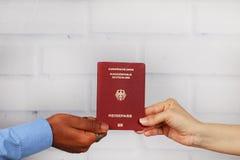 Biel ręki i czarne ręki trzyma niemieckiego paszport Fotografia Stock