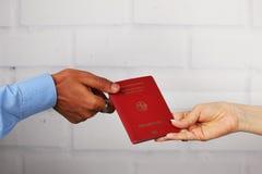 Biel ręki i czarne ręki trzyma niemieckiego paszport Obraz Royalty Free