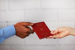 Biel ręki i czarne ręki trzyma niemieckiego paszport Zdjęcia Stock