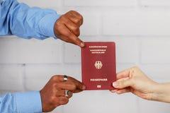 Biel ręki i czarne ręki trzyma niemieckiego paszport Fotografia Royalty Free
