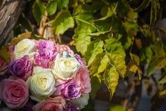 Biel srebne obrączki ślubne na bukiecie różowe i białe róże Liście w tle fotografia stock