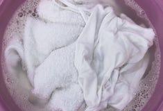 Biel ubrania z mydlanymi bąblami w obmycie basenie, odgórny widok fotografia stock