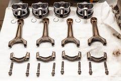Bielles et pistons de moteur utilisés et enlevés d'un moteur à quatre cylindres sur un tissu mou blanc dans un atelier de réparat photographie stock libre de droits