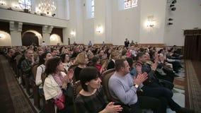 BIELORRUSIA, MINSK - 8 DE ABRIL DE 2015: El coro de los niños concierta Muchos hombres y mujeres se sientan en el concierto y apl almacen de video