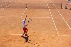 Bielorrusia, Minsk 26 05 18 El muchacho juega a tenis en la corte anaranjada de la suciedad Corte difícilmente fotografía de archivo