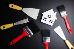 Bielu domu zabawka i farby muśnięcie, malarza wyposażenie na czarnym bac Fotografia Royalty Free