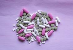 Bielu, menchii i zieleni pigułki na różowym tle, barwiący leki fotografia royalty free