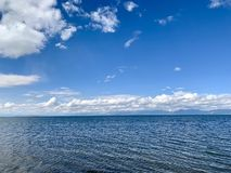Bielu niebieskie niebo nad jeziorem i chmury obraz royalty free