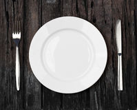 Bielu obiadowego talerza pusty położenie na starym ciemnym drewnianym stole obraz royalty free