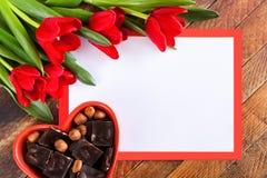 Bielu prześcieradło, czerwoni tulipany i serce kształtujący, rzucamy kulą z czekoladą dalej obrazy stock