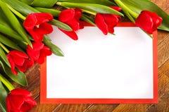 Bielu prześcieradło w czerwieni ramie z kopia astronautycznymi i czerwonymi tulipanami na woode obraz royalty free