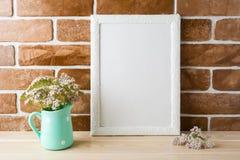 Bielu ramowy mockup z śmietankowymi menchiami kwitnie blisko odsłoniętych cegieł Obrazy Stock
