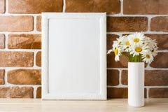Bielu ramowy mockup z stokrotka bukietem blisko wystawiał ściana z cegieł Fotografia Stock