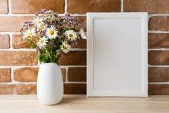 Bielu ramowy mockup z wildflowers bukietem blisko wystawiał cegłę w Zdjęcia Stock
