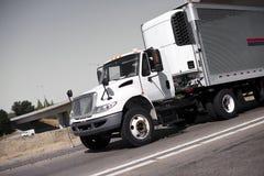 Bielu semi ciężarówka i stali nierdzewnej chłodziarki przyczepa na hig Zdjęcia Royalty Free