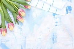 Bielu stół z barwionym błękitem Talerz dla lunchu i białego ręcznika Nóż i rozwidlenie Wiosna bukiet tulipany Bezpłatna przestrze Zdjęcie Stock