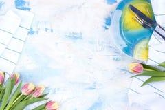 Bielu stół z barwionym błękitem Talerz dla lunchu i białego ręcznika Nóż i rozwidlenie Wiosna bukiet tulipany Bezpłatna przestrze Zdjęcia Stock