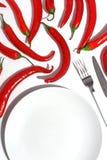 Bielu talerz, cutlery i korzenni czerwoni pieprze na jaskrawym stole, Cretive minimalistic pojęcie fotografia royalty free