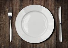 Bielu talerz, nóż i rozwidlenie na starym drewnianym stole, zdjęcia royalty free
