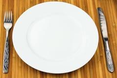 Bielu talerz, nóż i rozwidlenie przy bambusową pieluchą, Obrazy Stock