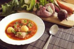 Bielu talerz z czerwonymi barszczami na stole blisko setu świezi warzywa i mięso Fotografia Stock